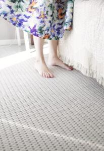 Füße von Frau auf teppichboden