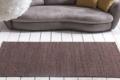 handwebteppich braun vor Sofa