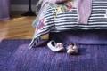 handgewebter teppich lila vor Bett