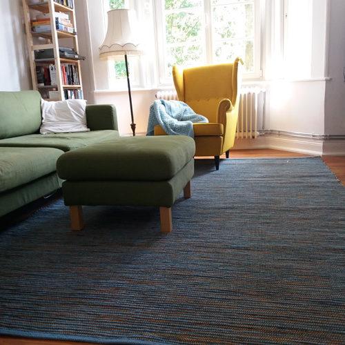 Teppich mit Hokcer und gelben Sessel